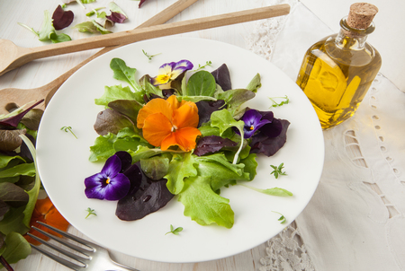 Lettuce and flower salad on woody white background spring, easter Archivio Fotografico