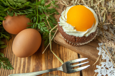 Easter cupcake on wooden background with Peach looks like a fried egg Standard-Bild