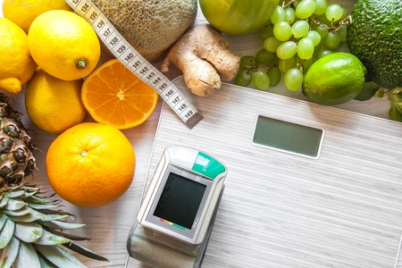 Flat lay composition with scales, healthy vegetables and fruit on wooden background. Weight loss diet Stok Fotoğraf