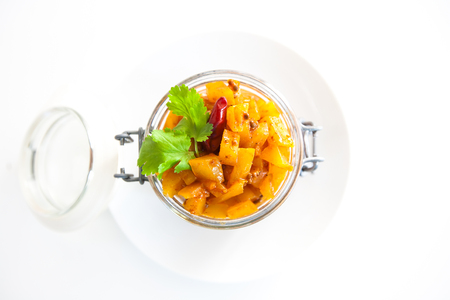 Homemade mango chutney in a glass jar with spices and mangoes isolated on a white background