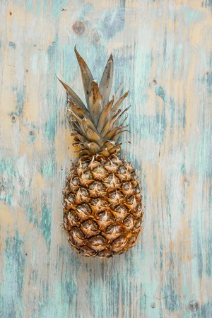 Pineapple isolated on blue wood background, ananas tropical fruit