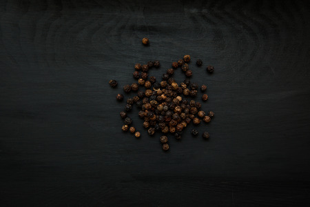 Close-up image of black pepper on black wood background, view above