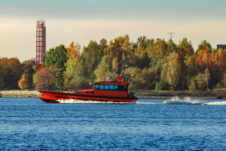 Red pilot ship moving past the autumn trees in Europe Stock Photo