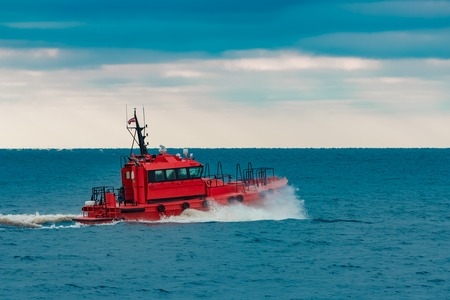 Red pilot ship sailing in still Baltic sea water