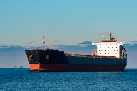 Black cargo ship moving in still Baltic sea water. Riga, Europe Stock Photo