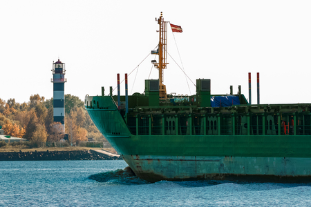 ship bow: Green cargo ships bow against lighthouse in still water, Riga