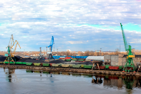 Baltic coal terminal with port cranes near the river. Riga cargo terminal