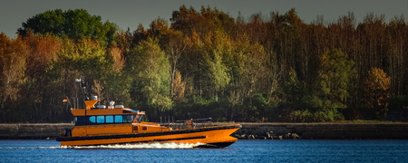 Orange pilot ship sailing past the autumn trees in Europe Stock Photo