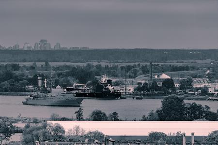 cinematic: Military ship sailing past the cargo port in Riga, Latvia