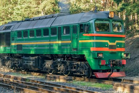 Green diesel cargo locomotive in forest