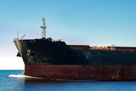 Black cargo ships bow in still water. Riga, Europe Stock Photo