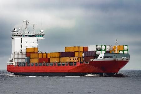 흐린 날에 발트 해에서 항해하는 빨간색화물 컨테이너 선박