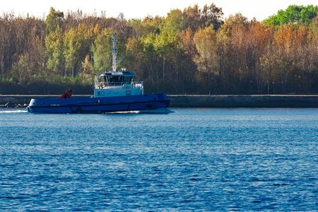 Blue small tug ship leaving Riga and entering the Baltic sea