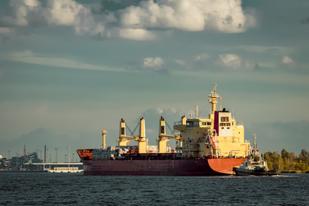 Red cargo ship and the tug ship towing it to the port Stock Photo