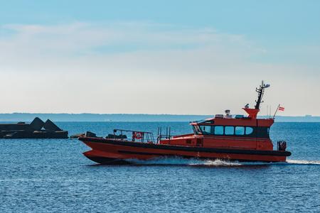 Orange pilot ship moving fast from Baltic sea