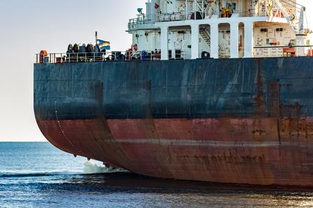 Black cargo ships stern in still water close up. Riga, Europe