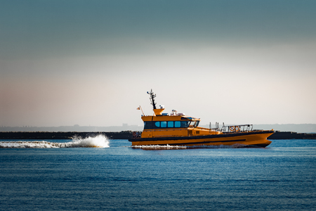 Orange pilot ship moving at speed past the breakwater dam