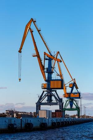 unloading: Yellow cargo cranes in the port of Riga, Europe