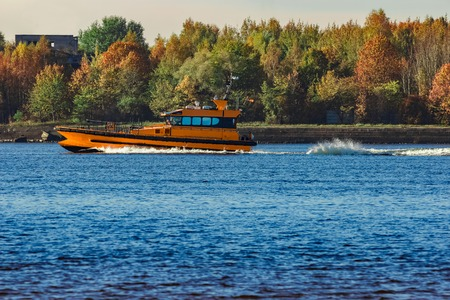 Orange pilot ship sailing past the autumn trees in Europe Stock Photo