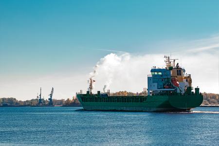 Green cargo ship entering a port of Riga, Europe
