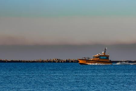 Orange pilot ship sailing from the Baltic sea in Latvia Stock Photo