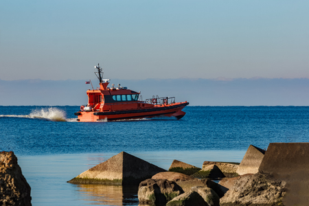 Red pilot ship moving at speed past the breakwater dam Stock Photo