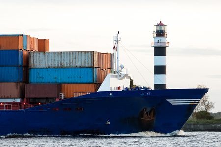 Blue container ships bow against big lighthouse, Latvia