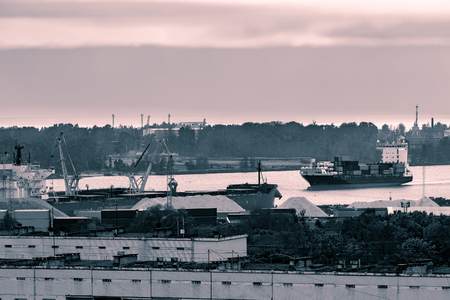 Red container ship entering port of Riga, Latvia