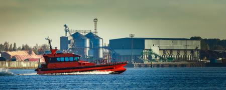 Red pilot ship moving past the factory in Latvia
