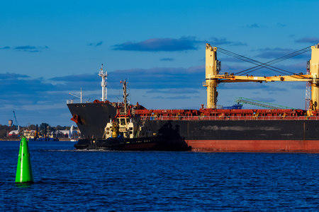 piloting: Black cargo ship mooring at the port with tug ship support Stock Photo