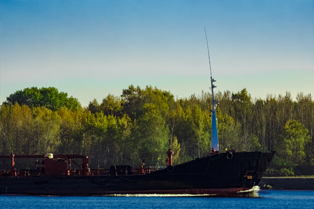 ship bow: Black cargo oil tankers bow against summer green trees Stock Photo