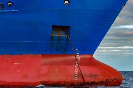 여전히 발틱 해 물에 정박 해있는 파란색 화물선