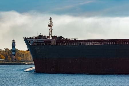 Black cargo ships bow entering Riga, Europe