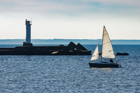 Small sailboat traveling past the lighthouse in sunny day