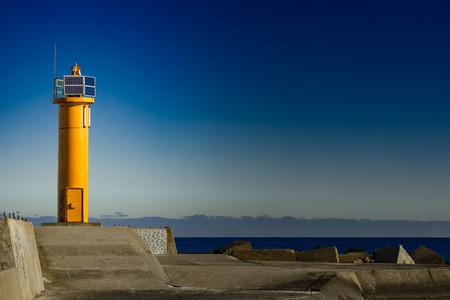 Yellow lighthouse on breakwater dam in Riga, Europe