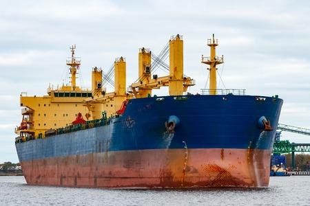 Blue cargo ship entering the port of Riga, Europe Stock Photo