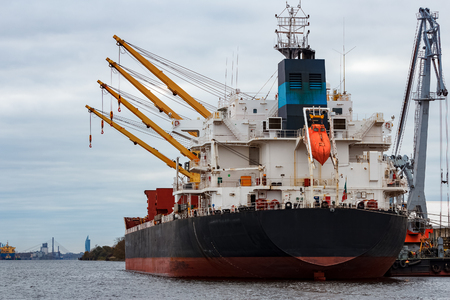 Black cargo ship loading in the port of Riga, Europe
