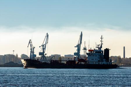 Black cargo oil tanker moving past the cargo cranes Stock Photo