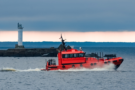 Red pilot ship moving at speed past the lighthouse in Riga Stock Photo