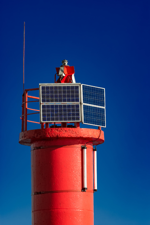 navigational light: Red lighthouse against blue sky in Riga, Europe Stock Photo