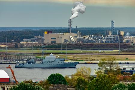 Military ship sailing past the cargo port in Riga, Latvia