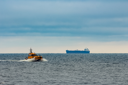 Orange pilot ship moving at speed in Baltic sea Stock Photo