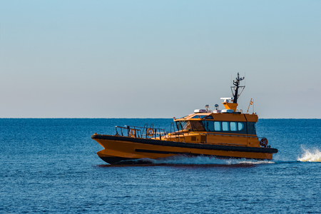 Yellow pilot ship moving at speed from the Baltic sea