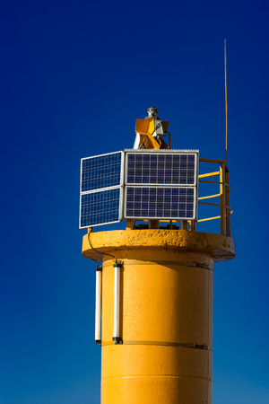 navigational light: Yellow lighthouse against blue sky in Riga, Europe