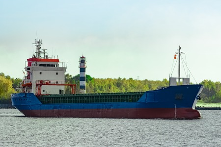 Blue cargo ship leaving the port of Riga at sunny day