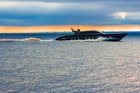 Barco negro del motor de la velocidad de la élite que se mueve rápidamente del mar Báltico Foto de archivo - 76051024