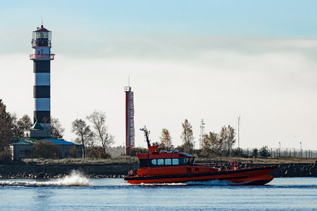 Red pilot ship sailing past the lighthouse in Riga Stock Photo