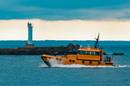 Orange pilot ship moving at speed past the lighthouse in Riga Stock Photo