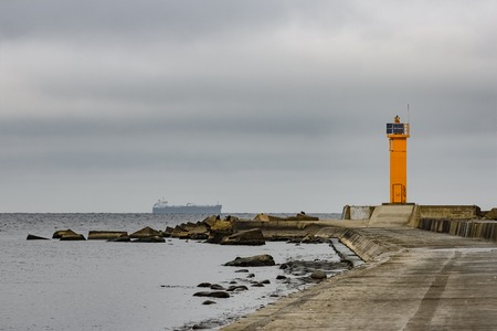 Breakwater dam with yellow lighthouse in Riga, Europe