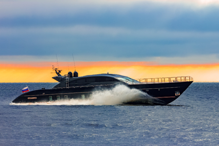 Black elite speed motor boat moving fast from Baltic sea
